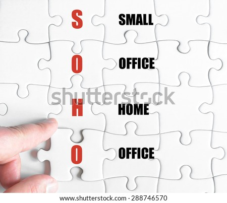 Hand of a business man completing the puzzle with the last missing piece.Concept image of Business Acronym SOHO as Small Office Home Office - stock photo