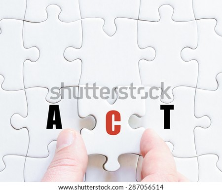 Hand of a business man completing the puzzle with the last missing piece.Concept image of puzzle board with motivational word ACT