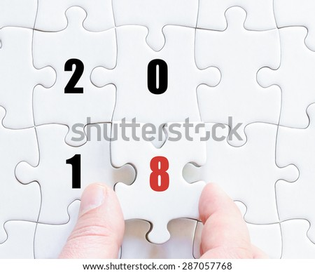 Hand of a business man completing the puzzle with the last missing piece. Concept image of puzzle board with year 2018