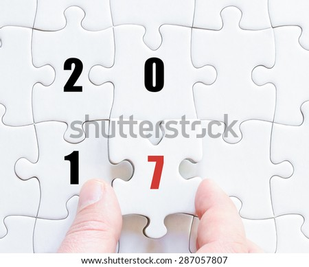 Hand of a business man completing the puzzle with the last missing piece. Concept image of puzzle board with year 2017