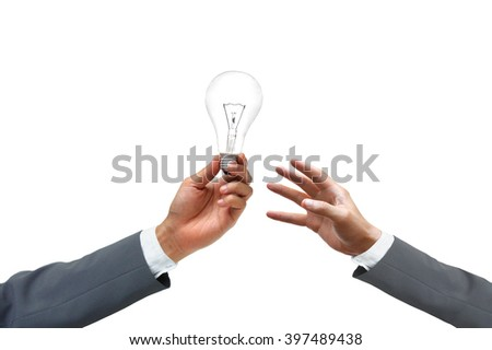 Hand of a businessman giving a light bulb to other businessman / Business needs new idea and innovation concept - stock photo