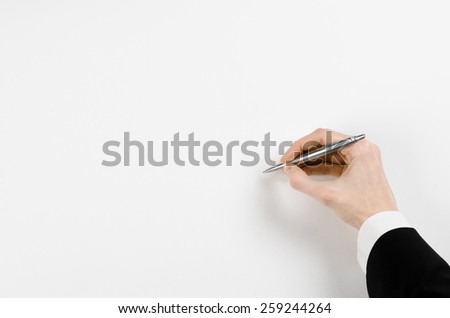 Hand of a businessman in a black suit holding a pen on a white sheet of paper