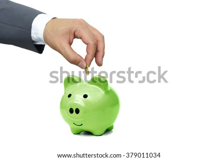 hand of a businessman putting a golden coin into a big  green piggy bank - green saving concept
