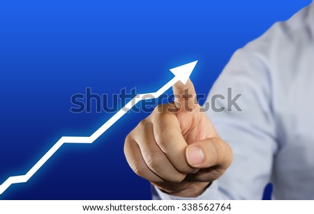 Hand of a businessman touching up arrow graphic on virtual screen over blue background