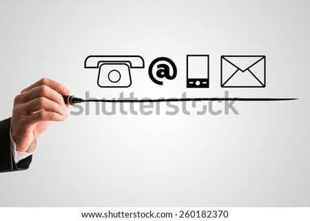 Hand of a businessman underlining contact icons on a grey virtual screen. - stock photo