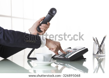 Hand of a businessman with dark gray suit holding the receiver of a black landline telephone while firmly pressing a button on telephone, with a cup of coffee and pens on a white office table.  - stock photo