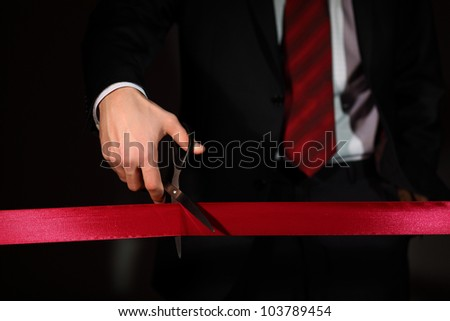 Hand of a businessman with scissors cuting a red ribbon - stock photo