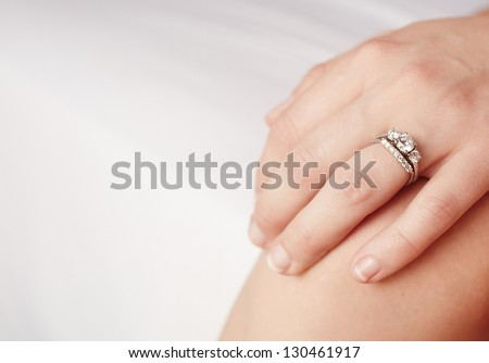 Hand of a caucasian adult woman with a diamond engagement ring on her left ring finger