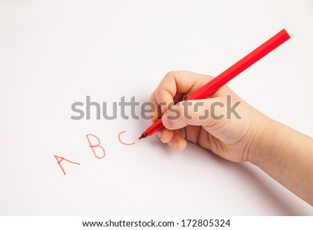 Hand of a child writing letters on white paper