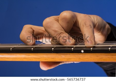Hand of a classic guitar players.Close up of fingers holding down a chord on the guitar.