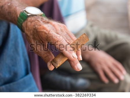 Hand of a Cuban senior holding a homemade cigar. Famous Cuban cigars are expensive and out of reach for most Cuban people. Seniors who know how to roll, produce their own cigars. - stock photo