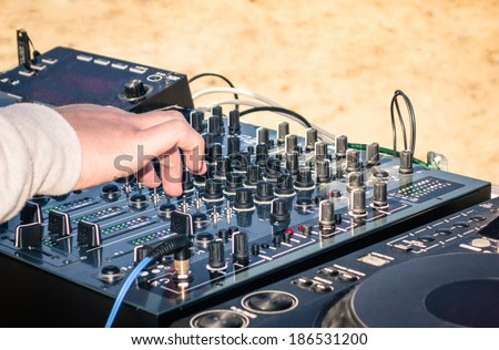Hand of a deejay playing music on professional mixing controller at the beach - stock photo