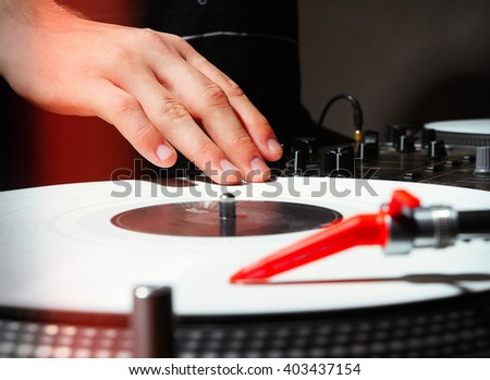 Hand of a DJ playing music on turntable with white vinyl record in dark studio or nightclub. Professional analog sound equipment - stock photo
