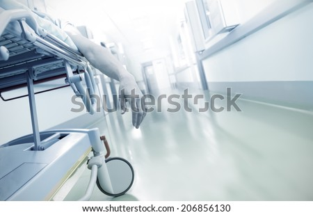 Hand of a dying patient lying on a mobile bed in hospital corridor  - stock photo