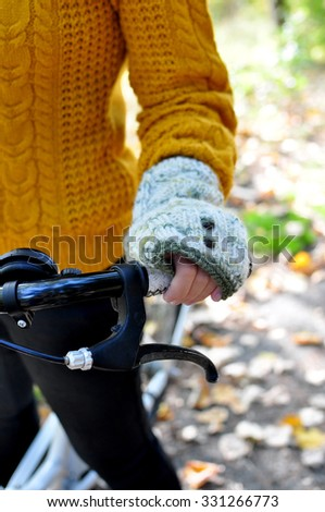 Hand of a girl in a knit glove holding a bicycle steer