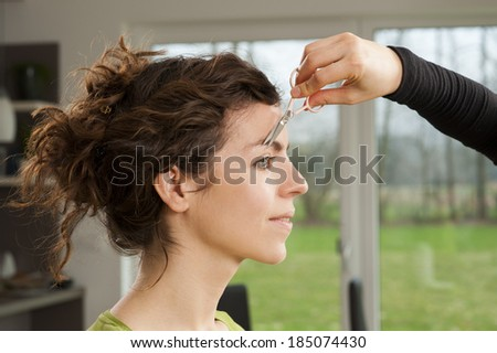 Hand of a make up artist and her model. She is getting here eyebrows done.  - stock photo