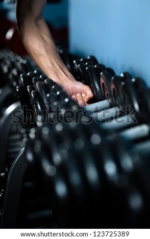 Hand of a man choosing a dumbbell out of set of black weights