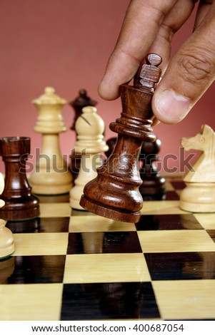Hand of a man going for checkmate - stock photo