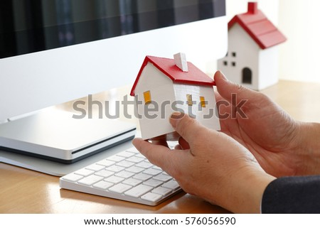 Hand of a man having the model of the house in front of a PC