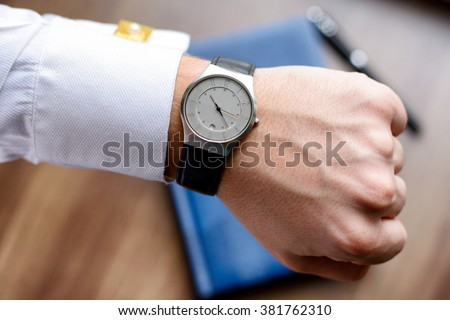 Hand of a man in white shirt with gold cufflinks with clock on a wooden desk with a notebook, fountain pen