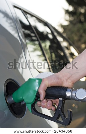 Hand of a man pumping gas in silver car