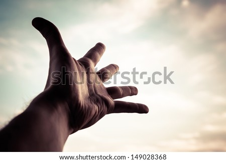 Hand of a man reaching to towards sky. Color toned image. - stock photo