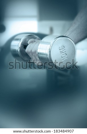 Hand of a man taking a dumbbell