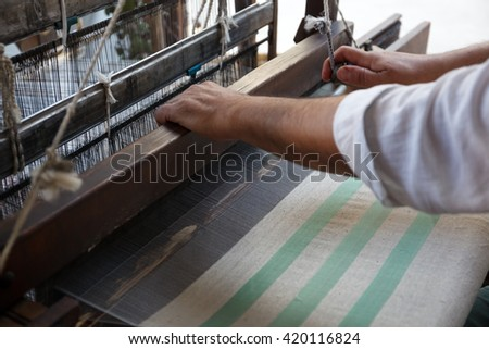 Hand of a man weaving traditional silk fabric - stock photo