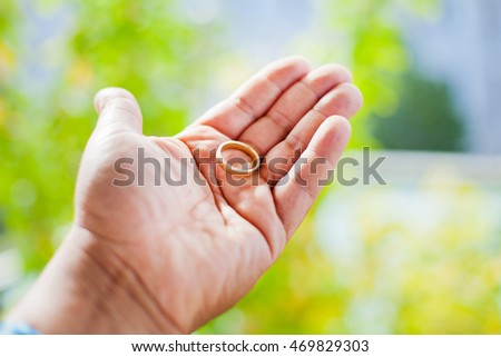 Hand of a man with a wedding ring in front of green plants.