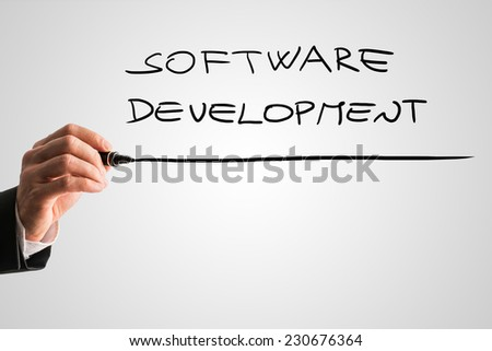 Hand of a man writing Software development on a virtual screen or interface with a marker pen with copyspace below.