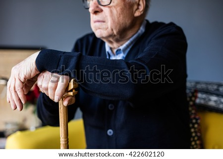 Hand of a old man holding a cane - stock photo