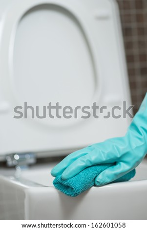 Hand of a person cleaning the toilet seat in rubber gloves with a sponge disinfecting the underside for germs and bacteria while performing household chores - stock photo