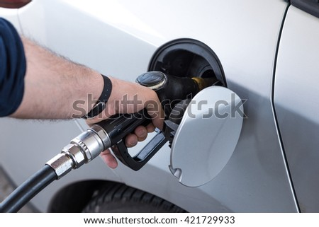 hand of a person intent on supplying diesel his car at a gas station
