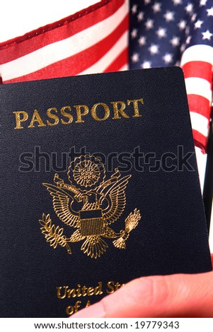 Hand of a proud American citizen holding a United States of America passport and a US flag to show his new USA naturalization citizenship - stock photo