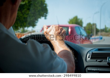 Hand of a senior man driving a car detail - stock photo