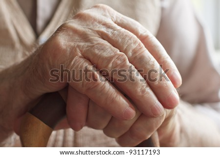 Hand of a senior man with a  cane - stock photo