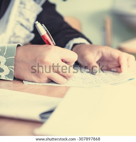 Hand of a student in a school uniform writes in a notebook. - stock photo