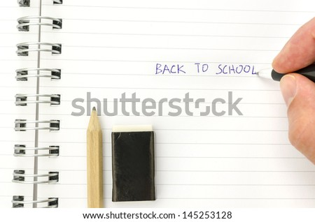 Hand of a student writing Back to school in spiral notebook. - stock photo