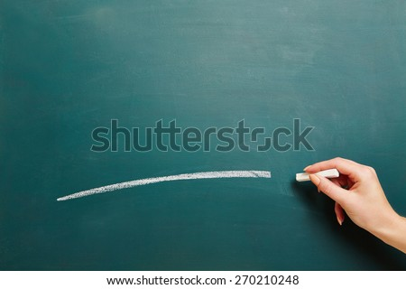 Hand of a teacher drawing white line with chalk on a green chalkboard - stock photo