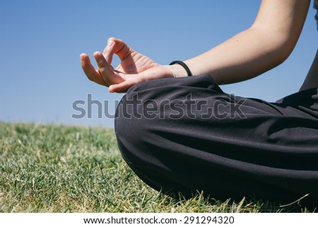 Hand of a woman doing yoga outdoors - stock photo