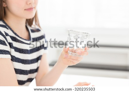 Hand of a woman drinking water