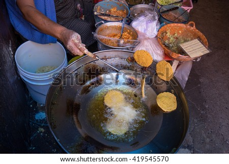 hand of a woman flipping deep fried gorditas in Queretaro Mexico