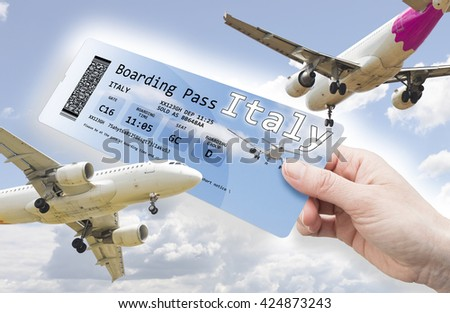 Hand of a woman holding a airplane ticket to Italy - concept image. The contents of the image are totally invented. The image background with the sky and the airplane are a picture of my property.