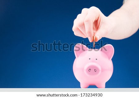Hand of a woman inserting a one dollar coin into a pink ceramic piggy bank. Photographed over a blue background. - stock photo