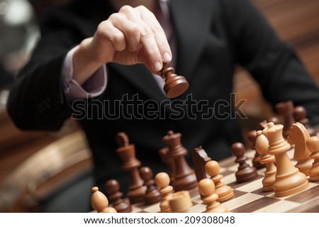 hand of a woman making a chess movement. Selective focus on the pawn. - stock photo