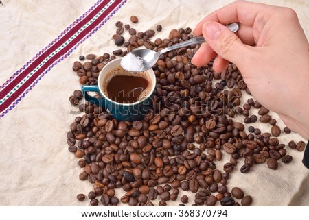 Hand of a woman mixing the sugar in a green cup of coffee. Roasted coffee beans on jute background. Aid waking in the morning. Morning pleasures - stock photo