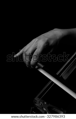 Hand of a woman playing the cello in black and white