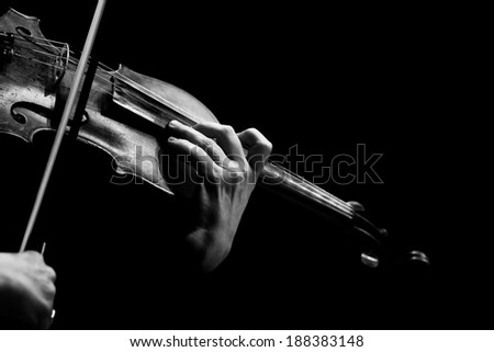 Hand of a woman playing violin on black background in black and white - stock photo