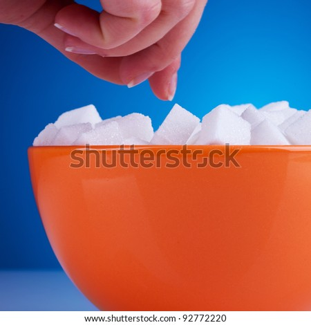 hand of a woman reaching for some sugar cubes on blue background - stock photo