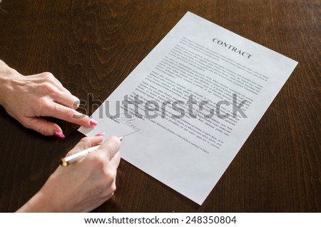 Hand of a woman signing a contract